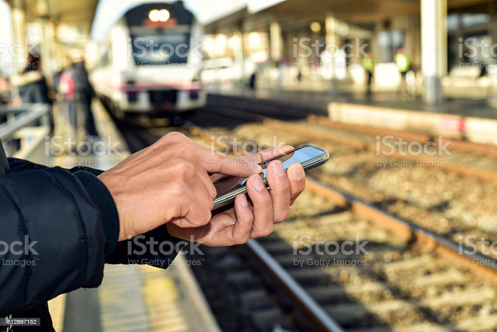 young man using a smartphone in  train station stock photo