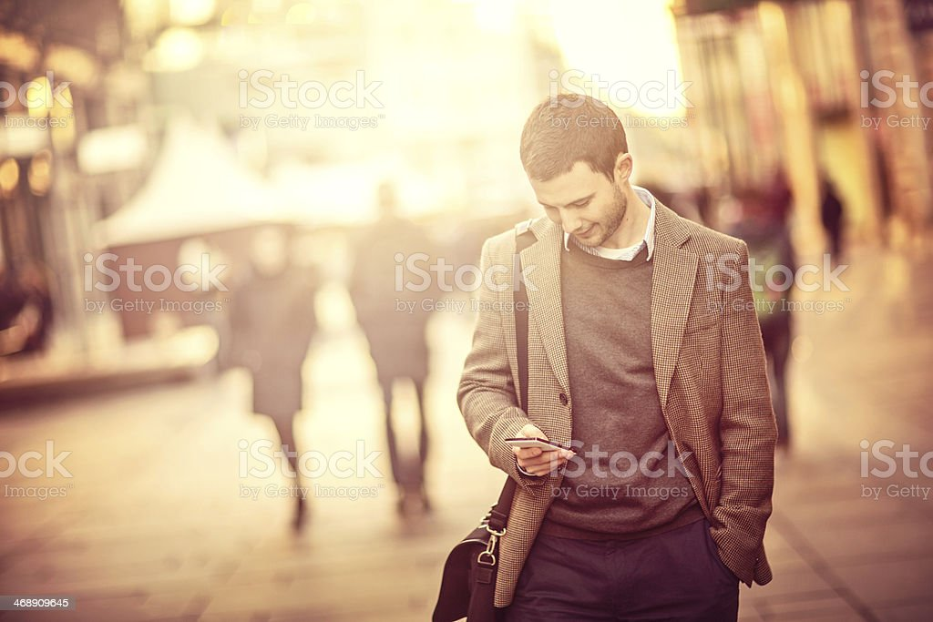 Young man using a smartphone on the street stock photo
