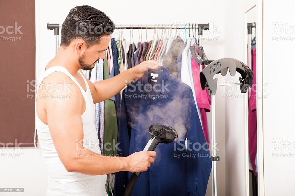 Young man using a steamer on his clothes stock photo