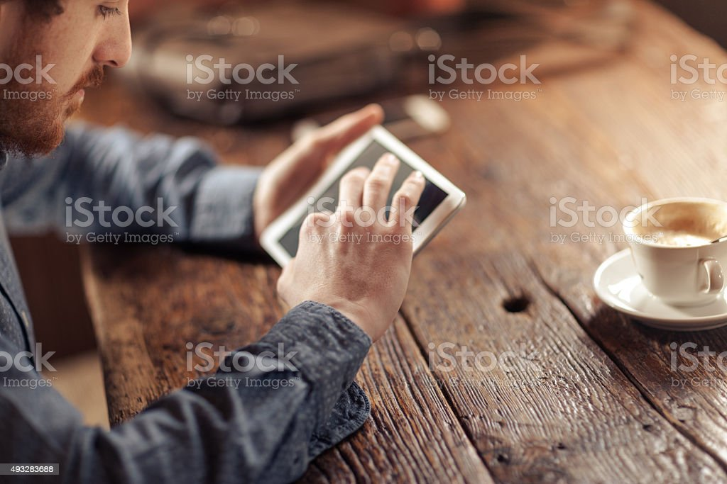 Young man using a touch screen tablet stock photo