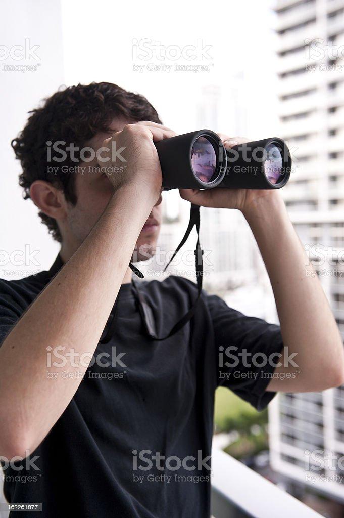Young man using binoculars stock photo
