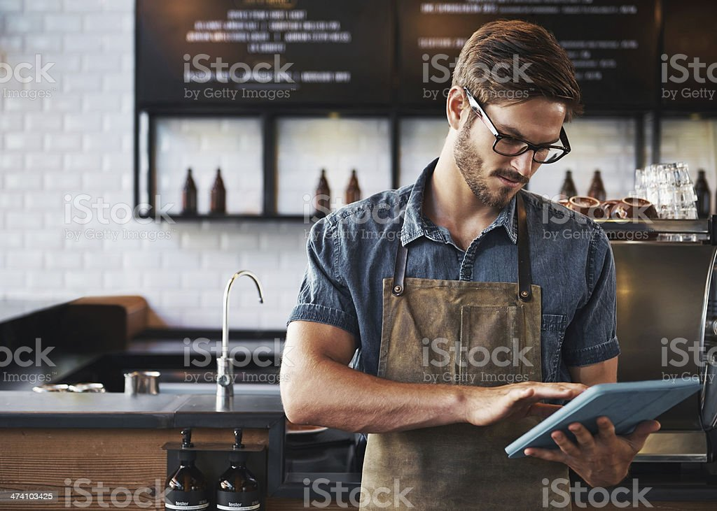 Young man using blue tablet in a cafe stock photo