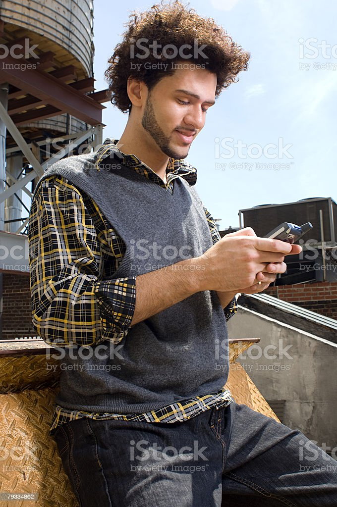 Young man using cell phone stock photo