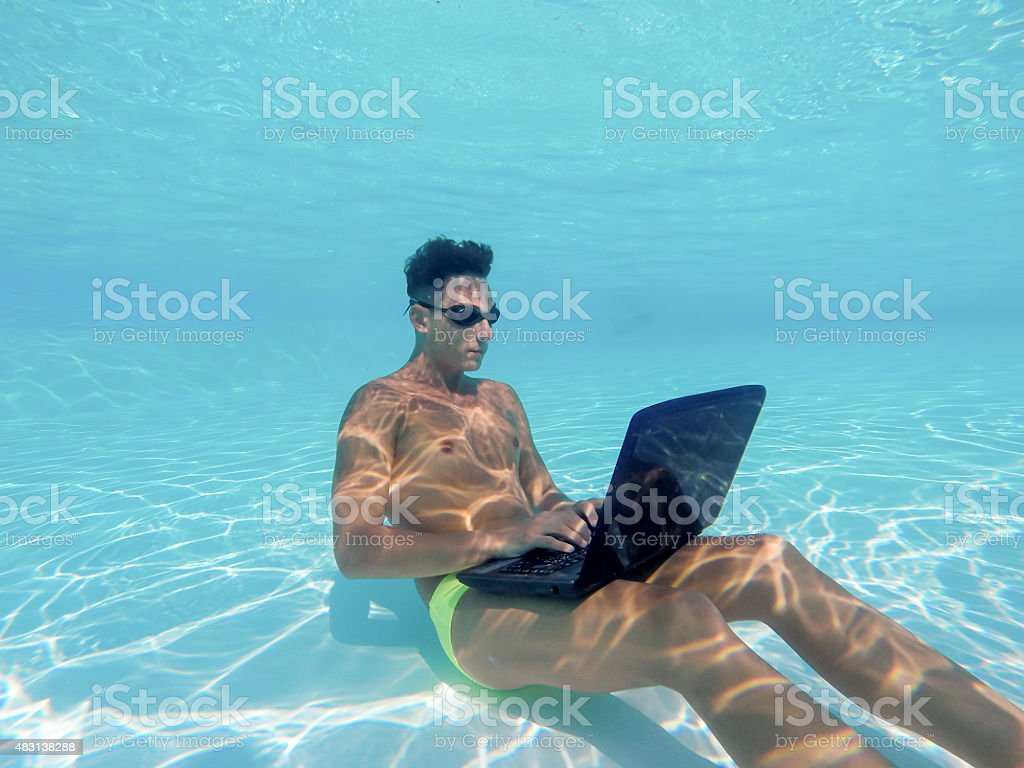 Young man using computer underwater stock photo
