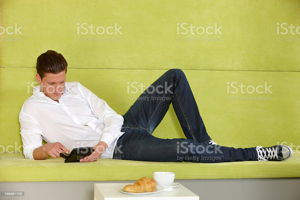 Young man using digital tablet at home royalty-free stock photo