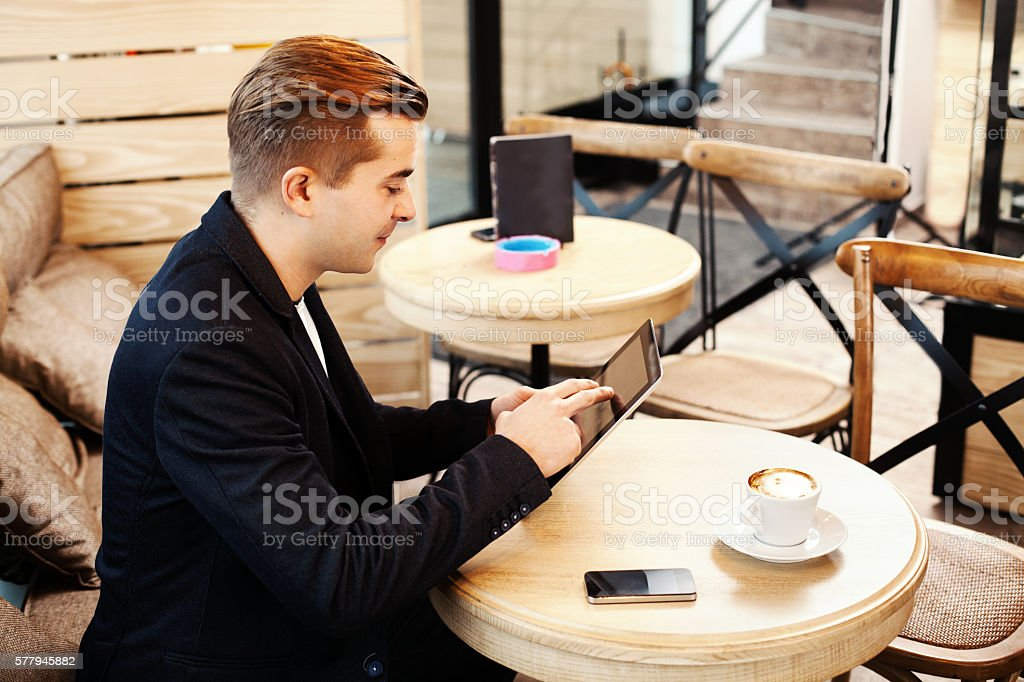 Young man using digital tablet in caffe stock photo