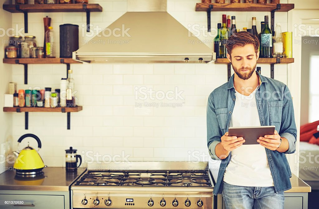 Young man using digital tablet in kitchen stock photo