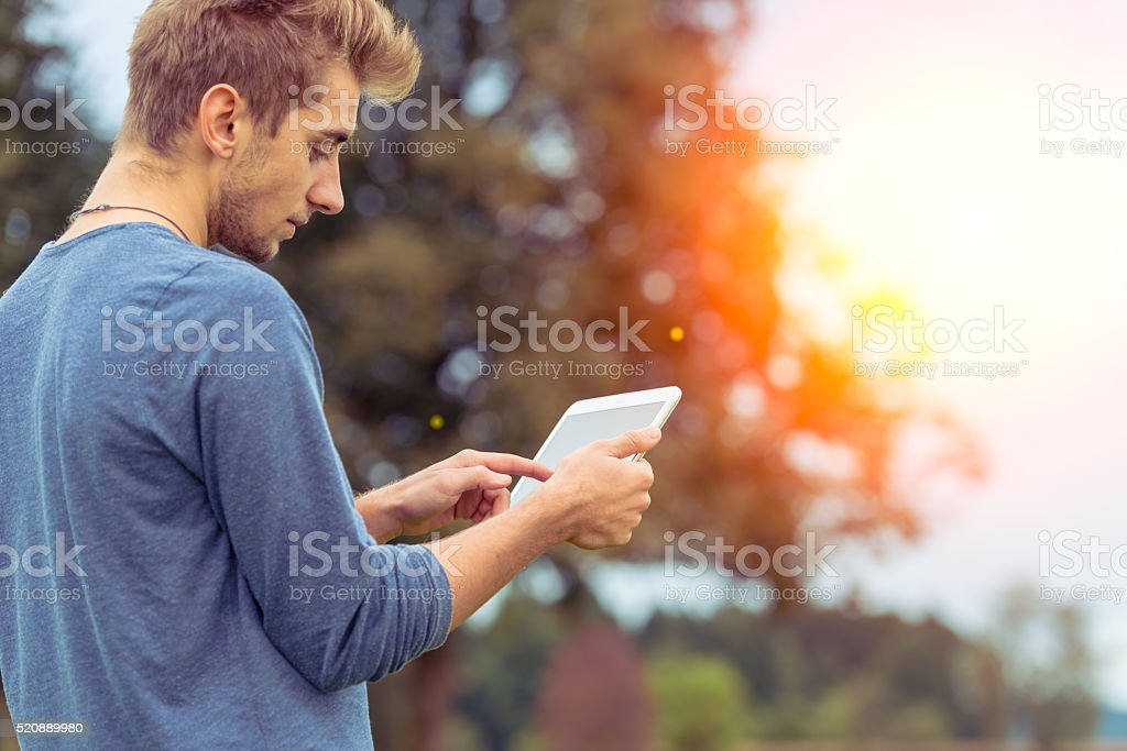 Young man using Digital tablet in nature stock photo