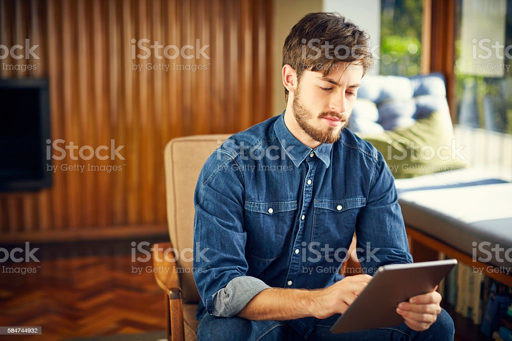 Young man using digital tablet on chair at home stock photo