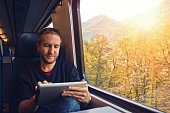 Young man using digital tablet on train