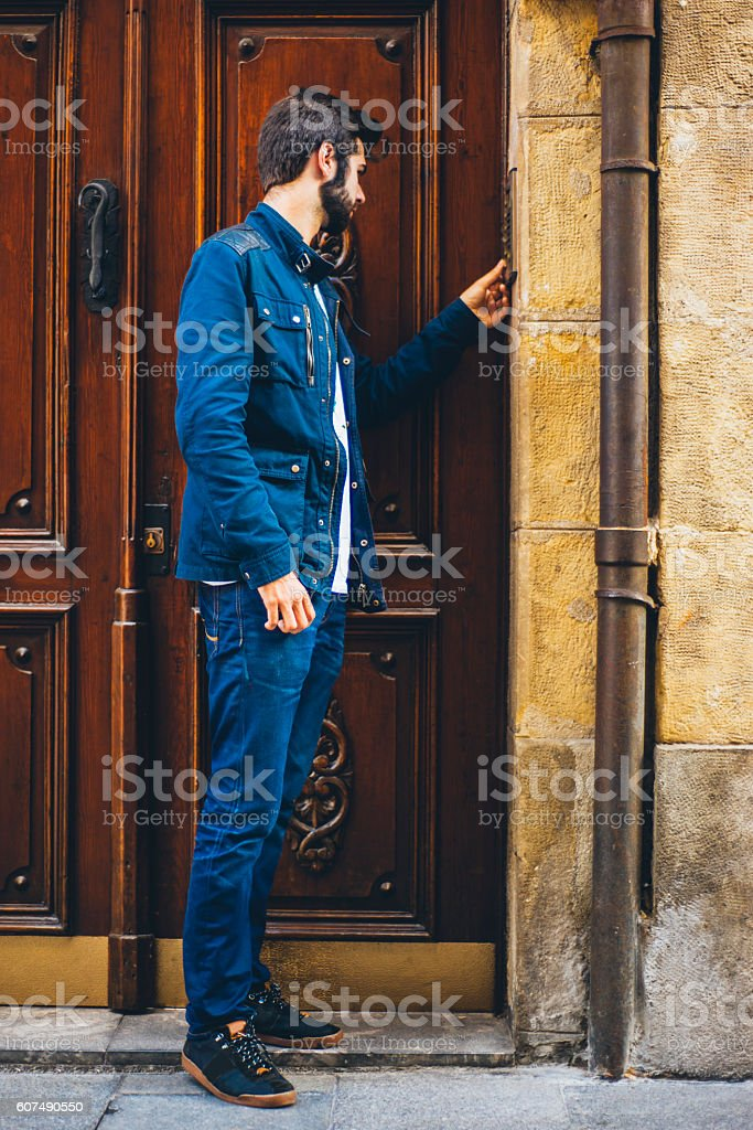 Young man using door security system stock photo