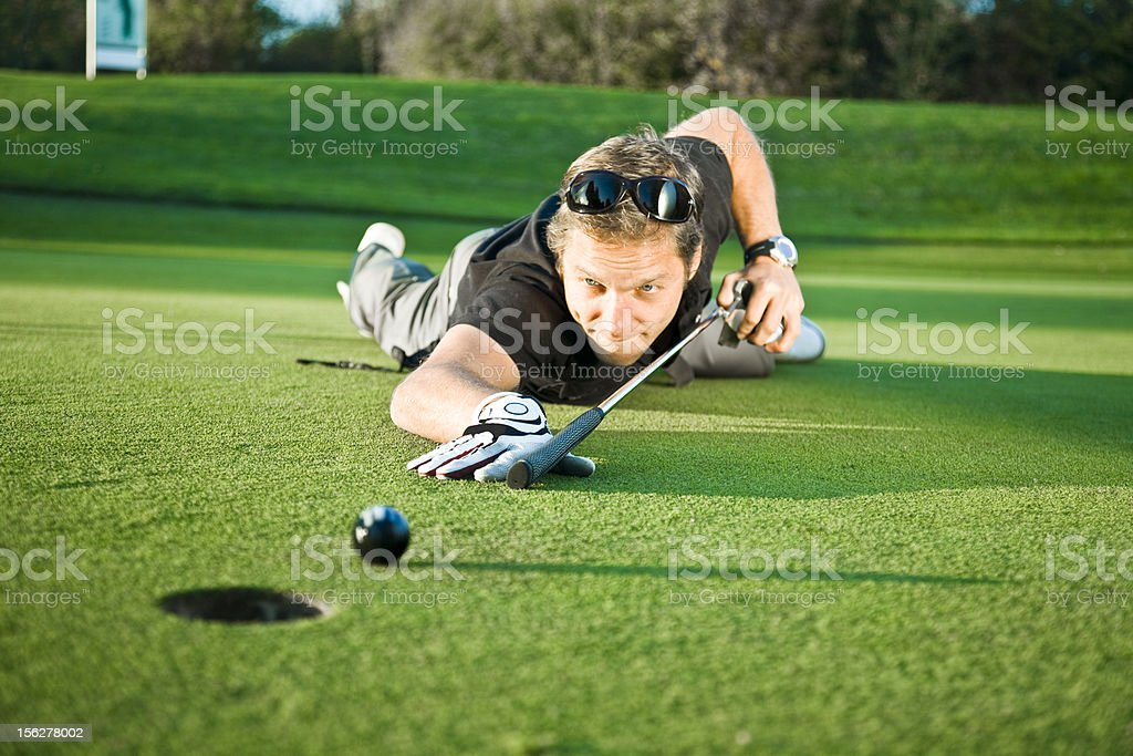 Young Man Using Golf Club as Billiard Queue on Green stock photo