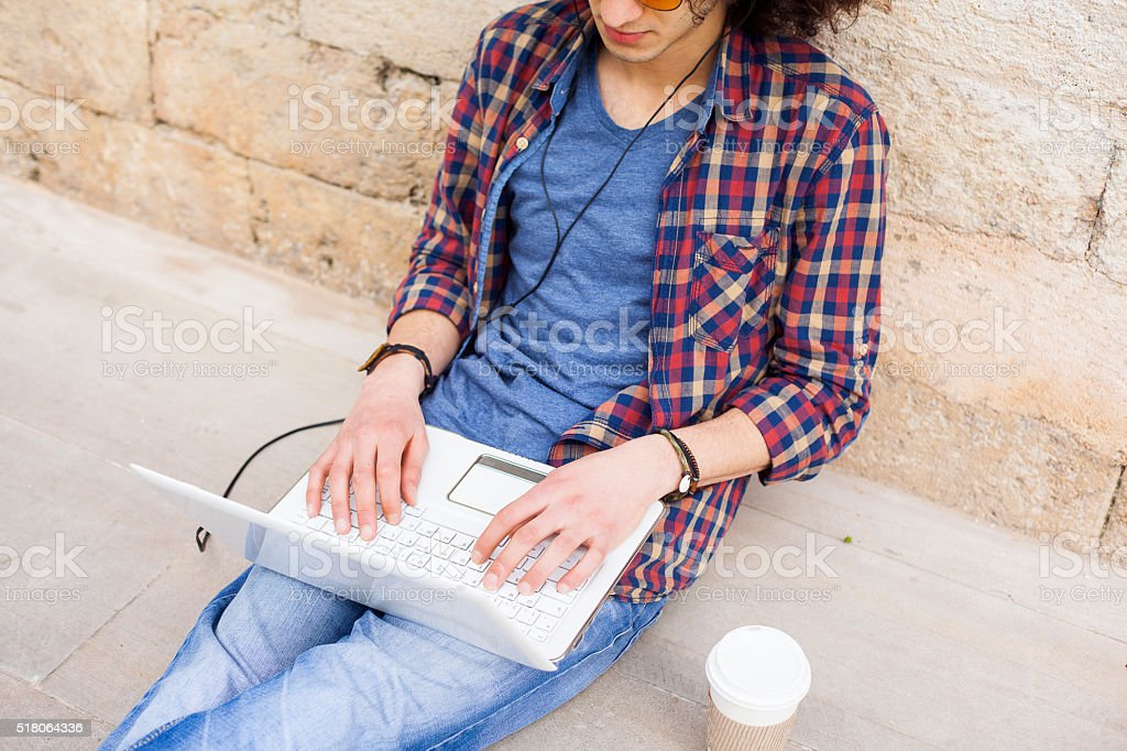 Young man using laptop and headphones stock photo
