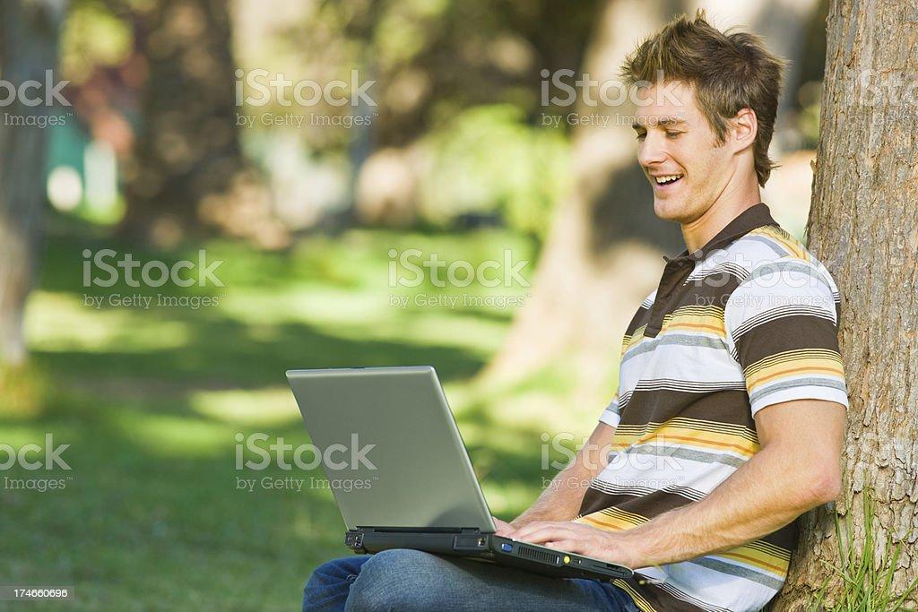 Young man using laptop at park royalty-free stock photo
