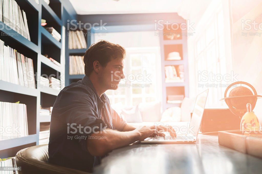 Young man using laptop at table stock photo