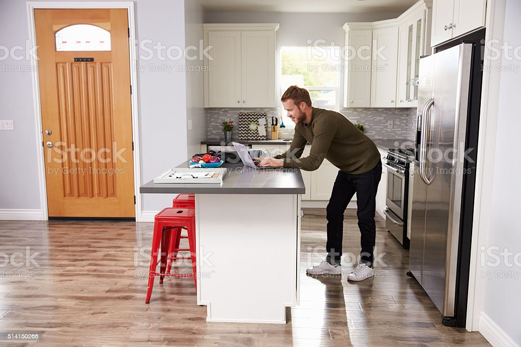Young Man Using Laptop In Apartment Kitchen stock photo