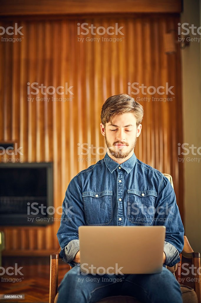 Young man using laptop on chair in living room stock photo