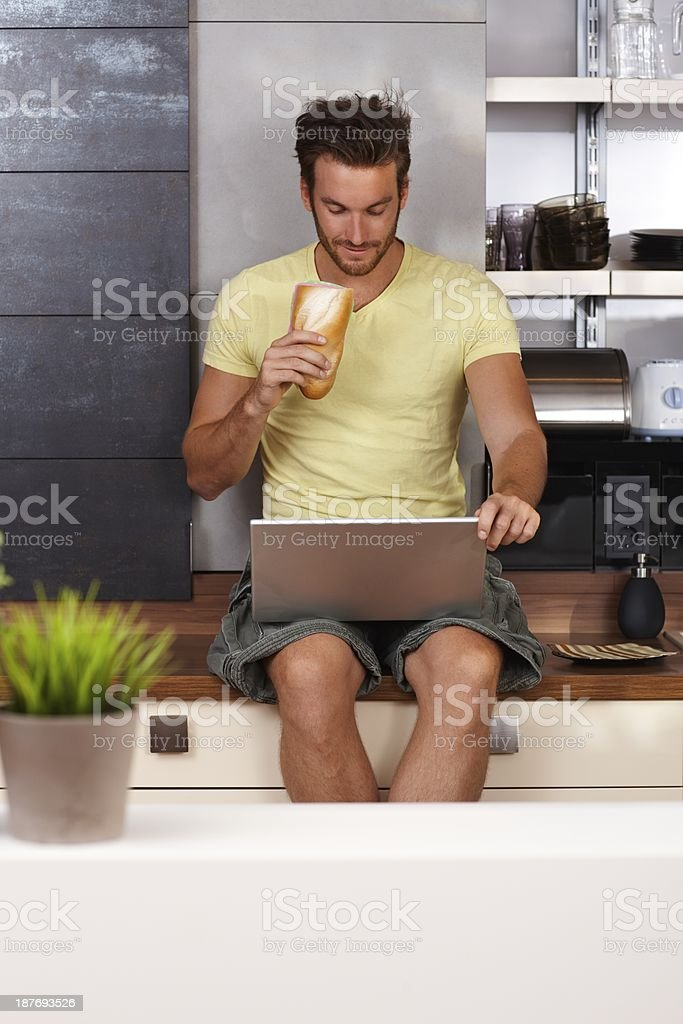 Young man using laptop on kitchen counter stock photo