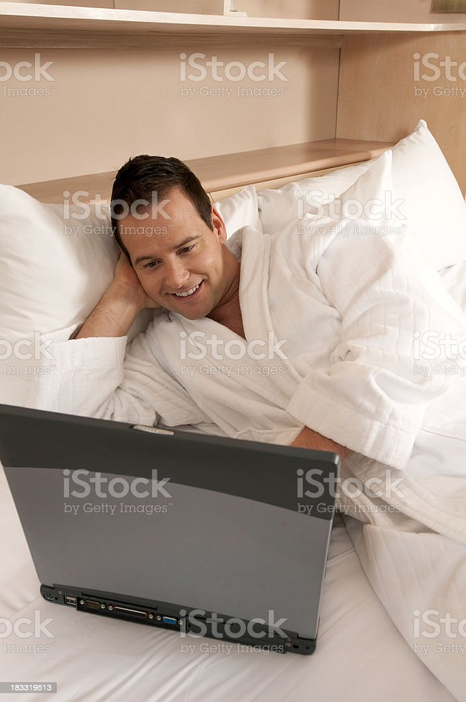 Young Man Using Laptop on Luxury Bed stock photo