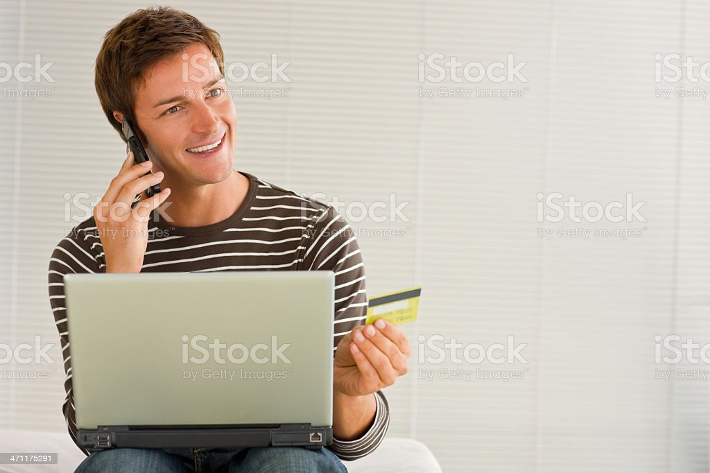 Young man using laptop, talking on cellphone holding credit card royalty-free stock photo