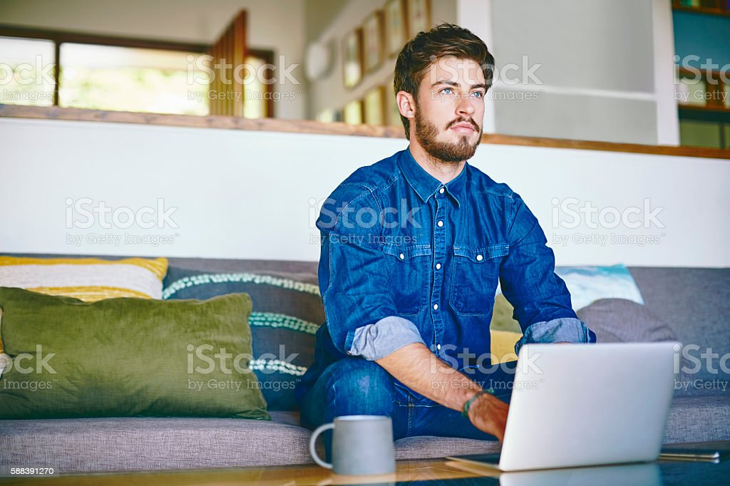 Young man using laptop while looking away at home stock photo