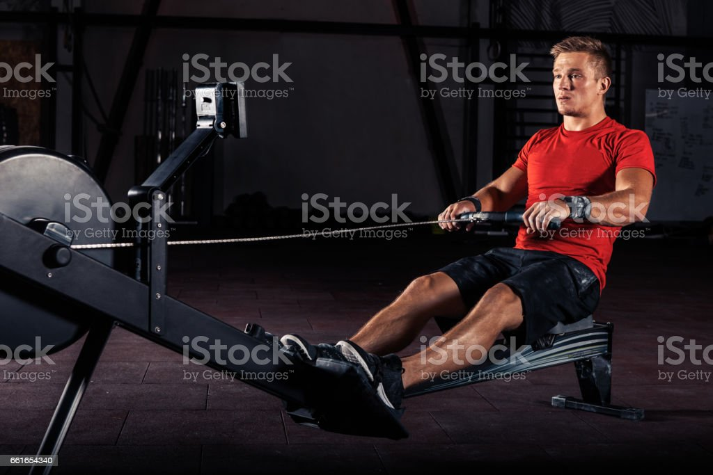 young man using rowing machine in the gym stock photo