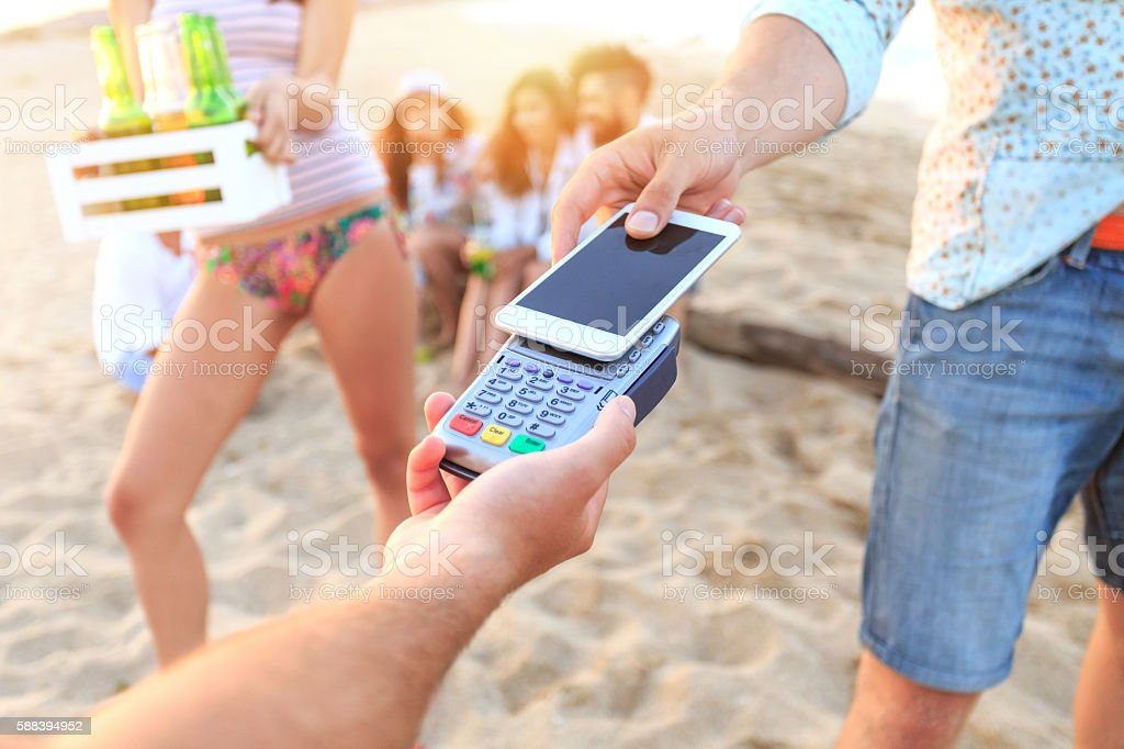 Young man using smart phone for contactless payment on beach stock photo