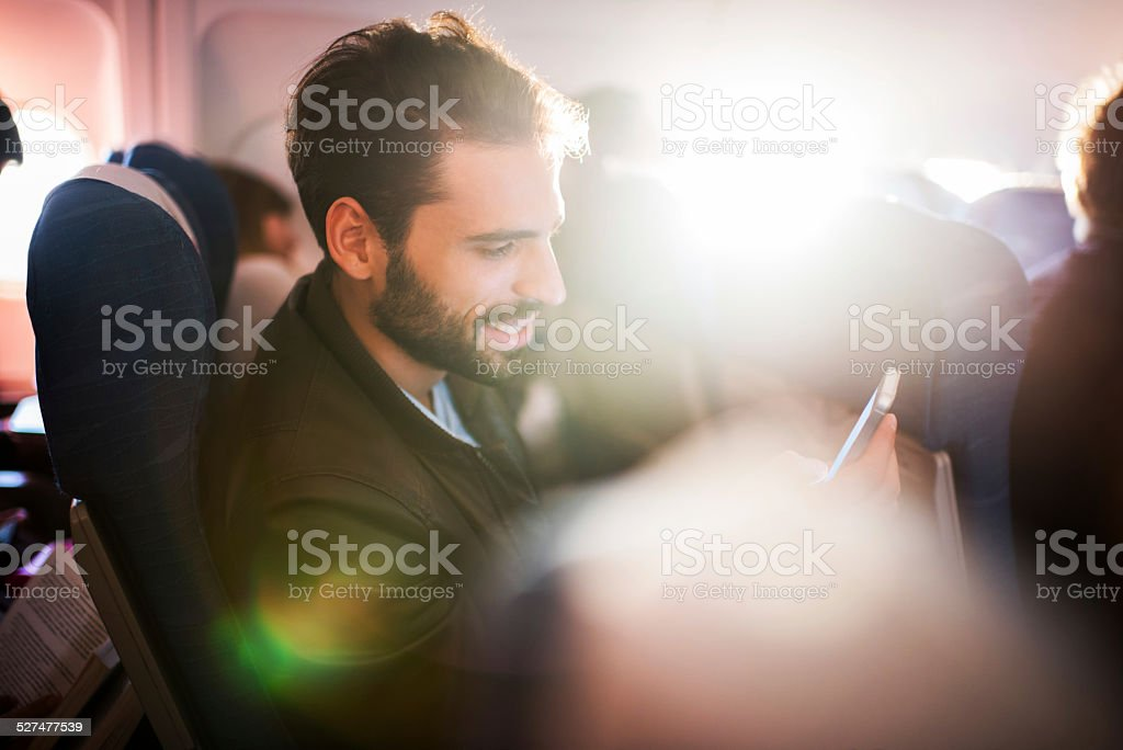 Young man using smart phone in airplane. stock photo