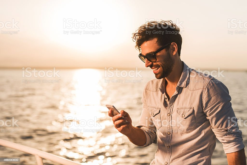 Young man using smart phone on a boat at sunset. stock photo