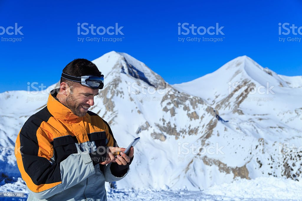 Young man using smart phone on top snow mountain stock photo