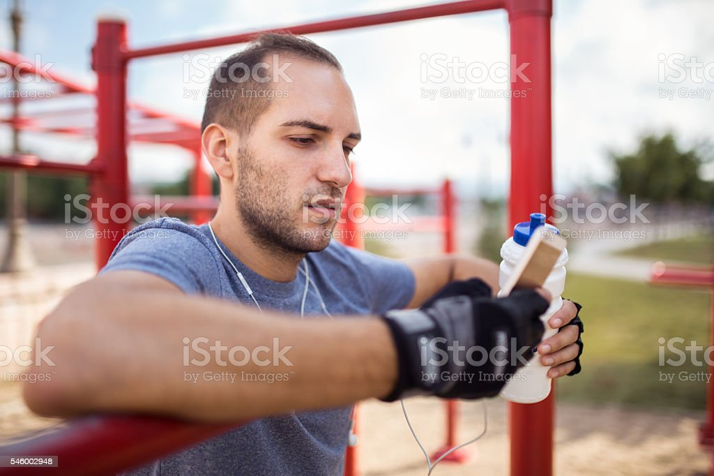 Young man using smart phone on training stock photo