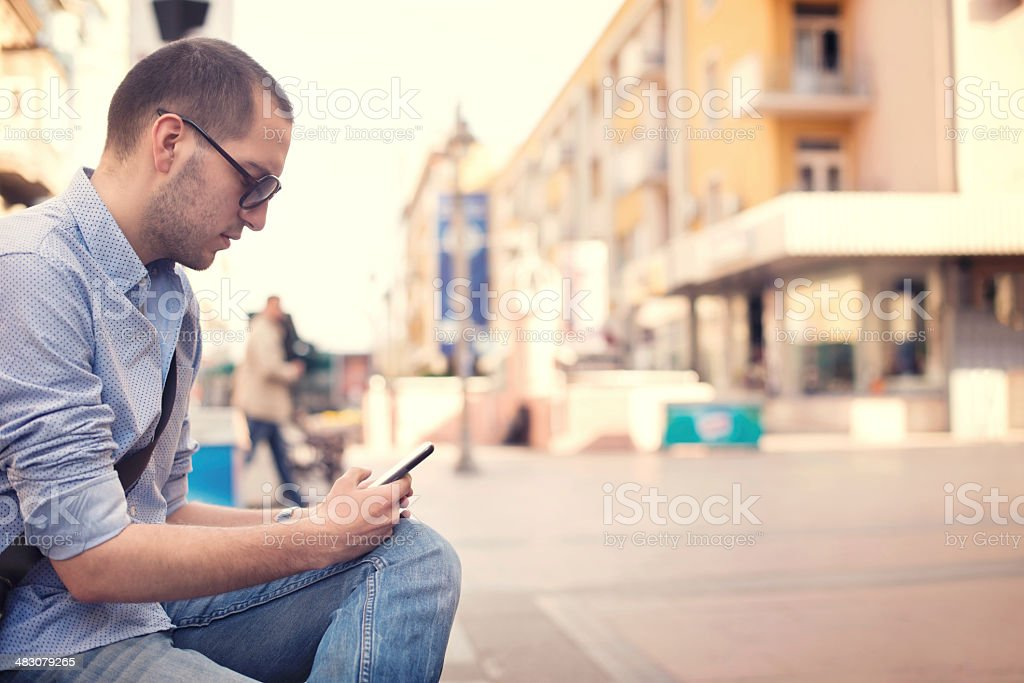 Young man using smartphone of street stock photo