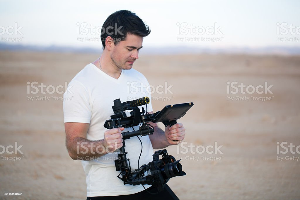 Young man using steadycam for shooting on beach stock photo