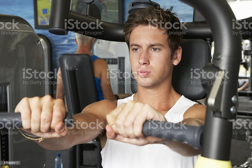 Young Man Using Weights Machine In Gym stock photo