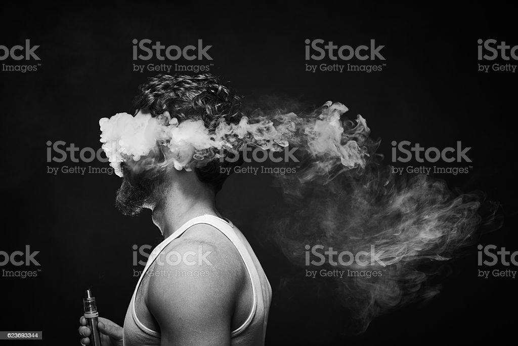 Young man vaping against black background stock photo