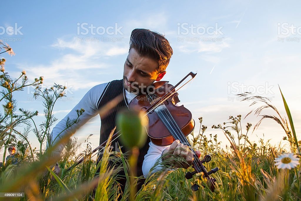 Young man violinist playing an violin stock photo