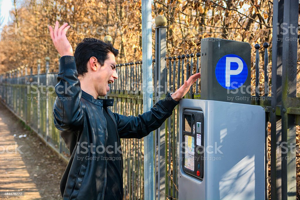 Young man waiting for a parking ticket stock photo