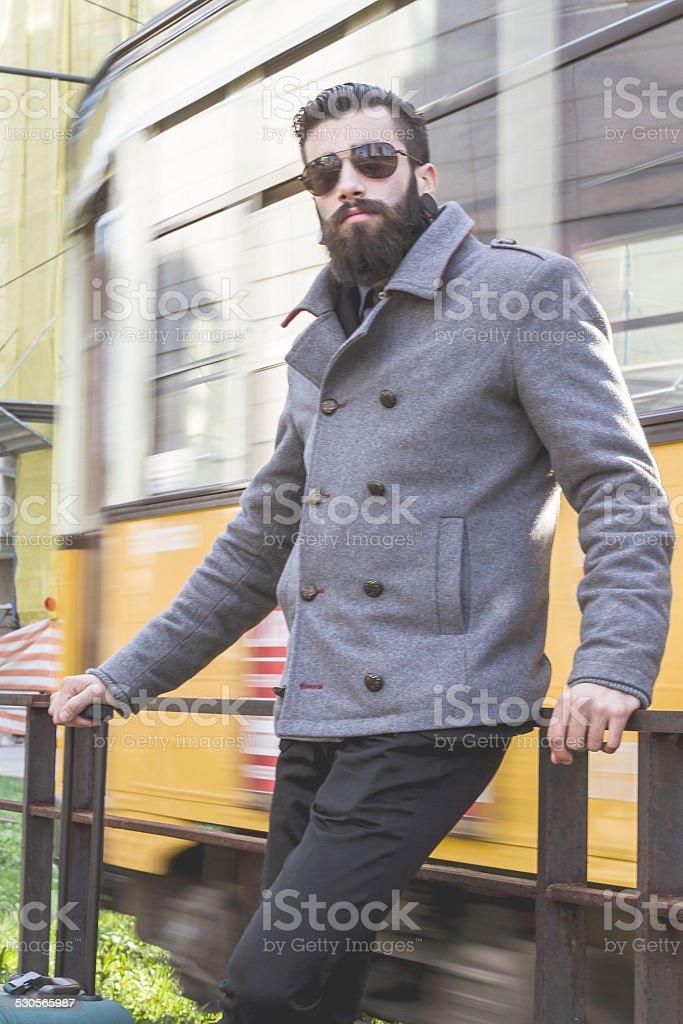 Young man (stylish hipster) waiting near tramway stock photo