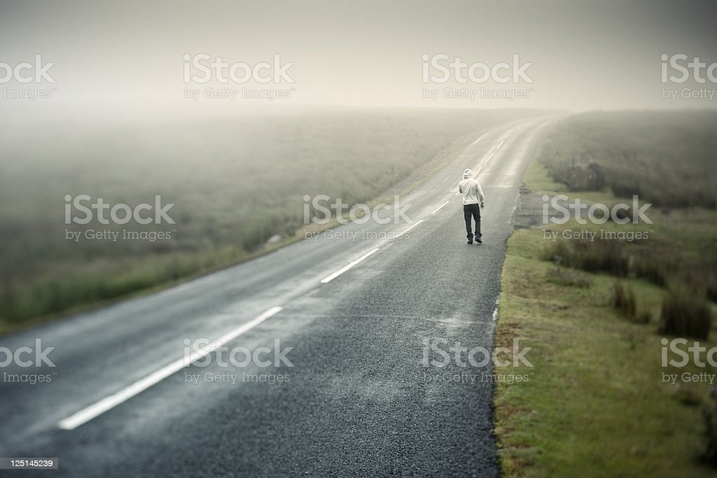 young man walking down a foggy country road. stock photo