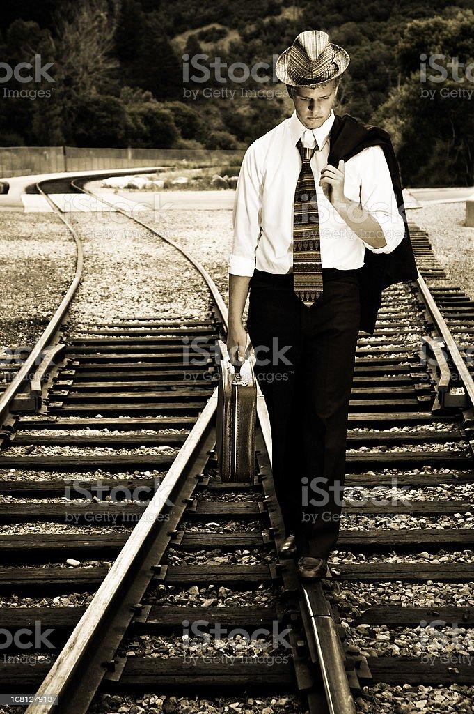 Young Man Walking Down Rail Road Tracks stock photo
