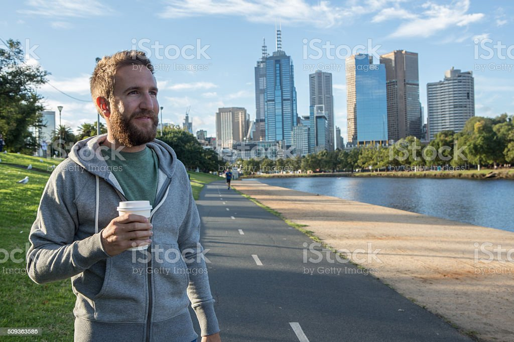 Young man walking in Melbourne city carries a takeaway coffee stock photo