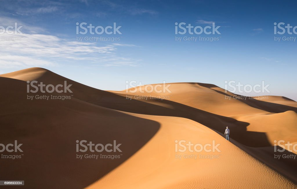 young man walking in the sand dunes of Liwa desert stock photo
