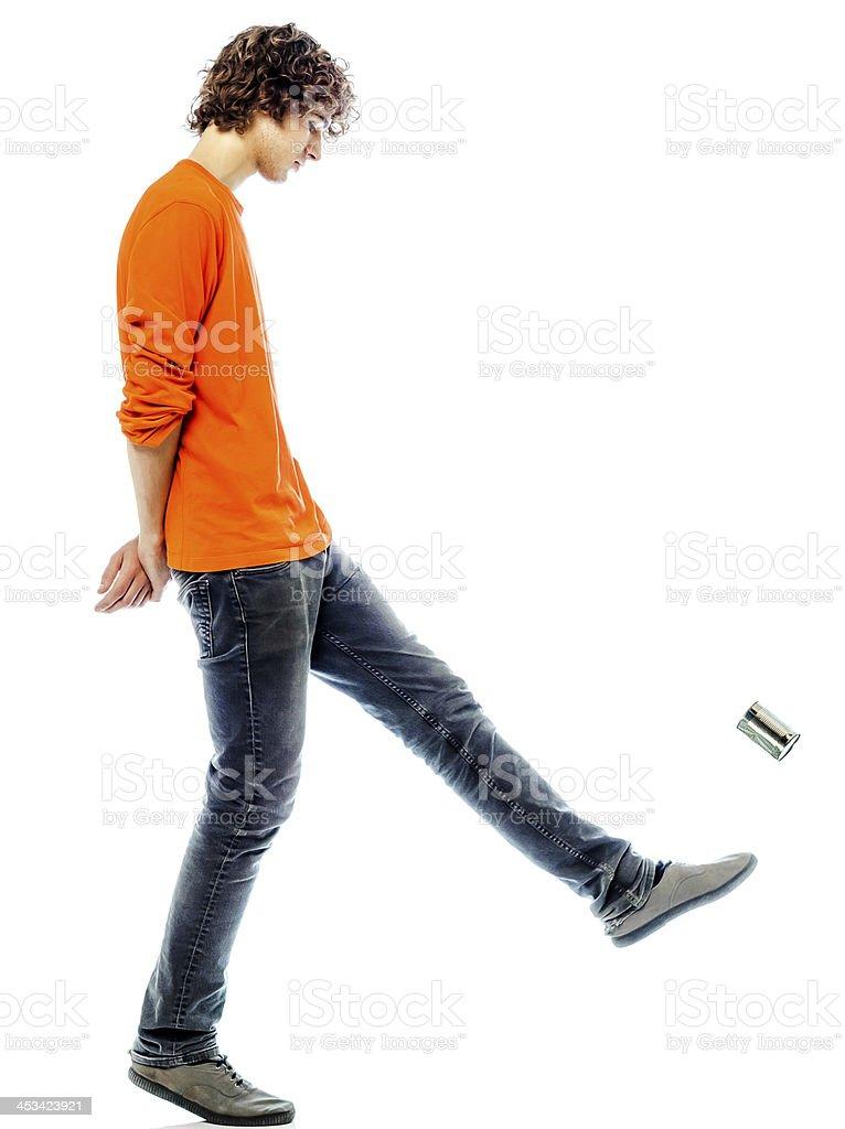 young man walking kicking tin can side view stock photo