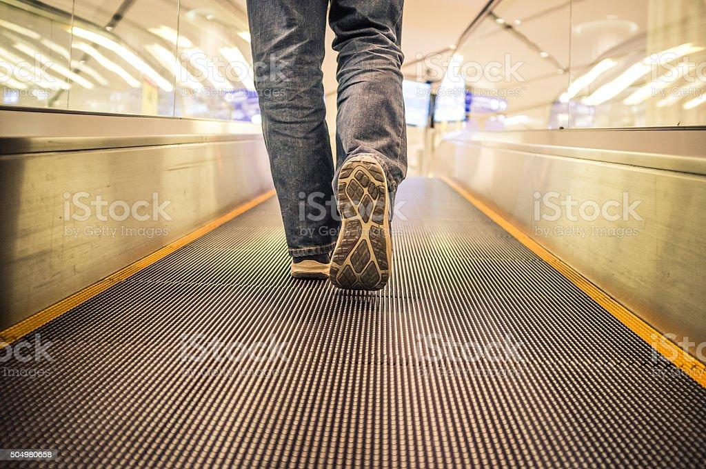 Young Man Walking on an escalator stock photo
