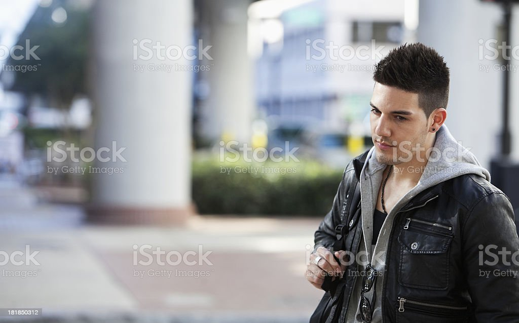 Young man walking on city street stock photo