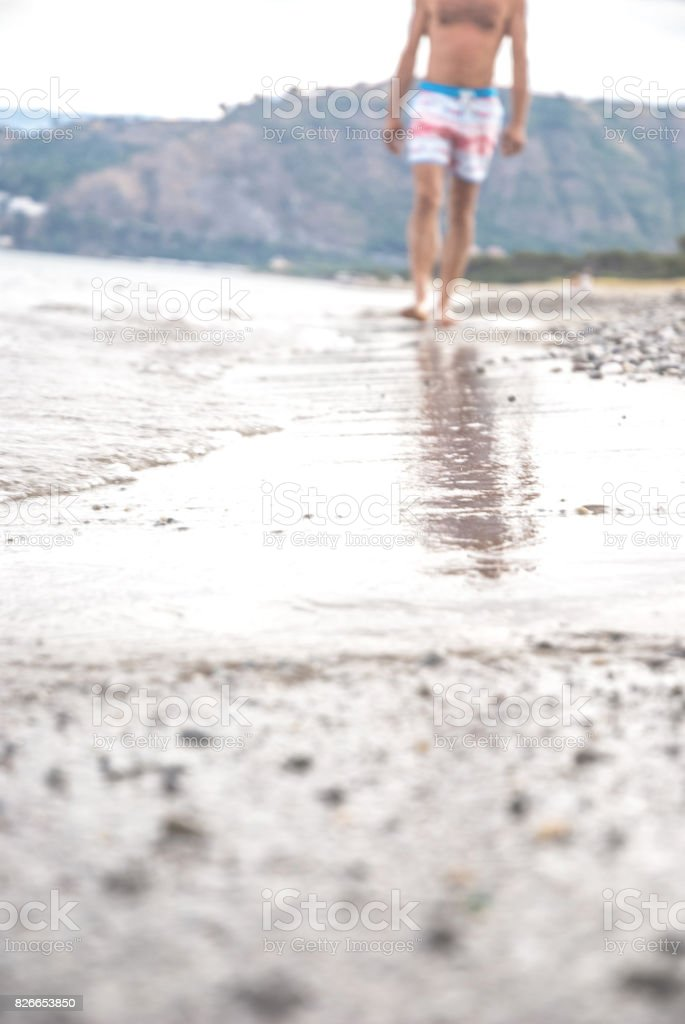 Young Man Walking on the Beach stock photo