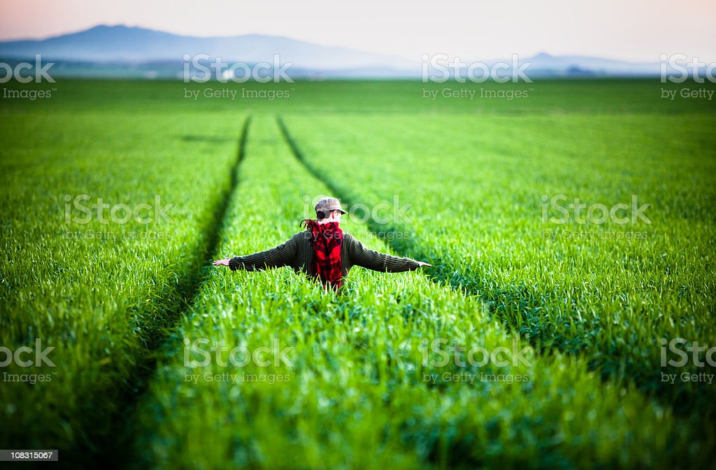 Young man walking through a fresh green field of grass royalty-free stock photo