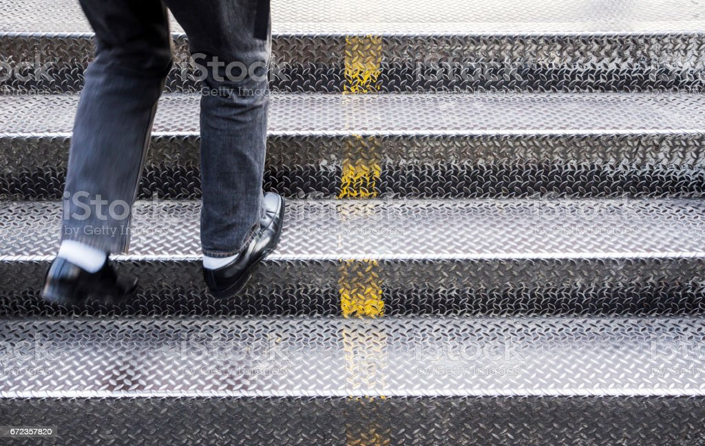 Young man walking up the stairs stock photo