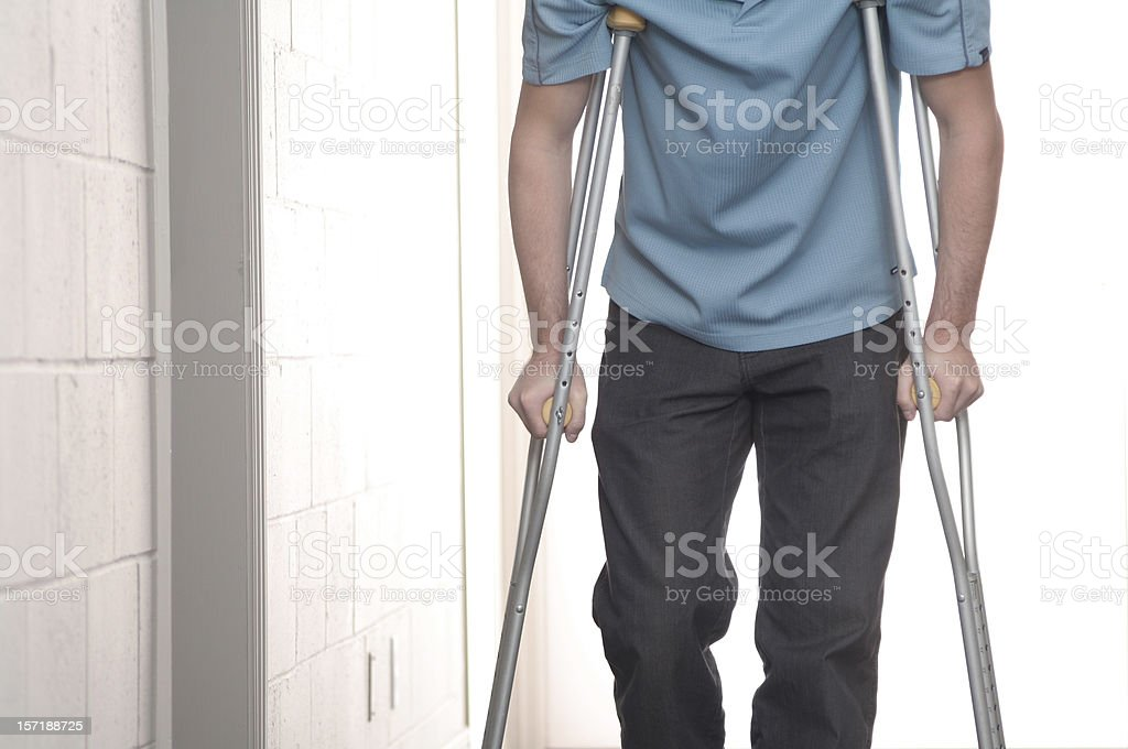 Young man walking with crutches stock photo