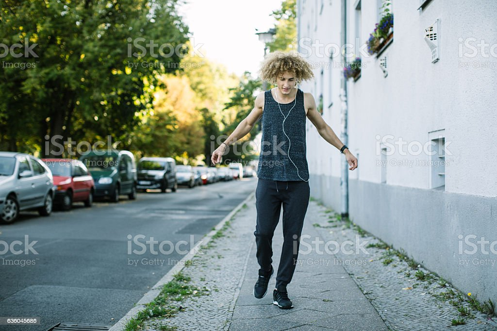 Young man warming up before morning run in city stock photo